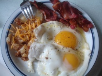Two_eggs_sunny_side_up,_bacon,_and_home_fries_with_cheddar_cheese